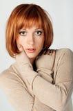 Portret van rood haired meisje met handen wat betreft FA Royalty-vrije Stock Afbeelding
