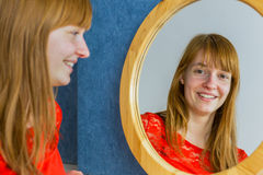 Portret van roodharigemeisje het kijken in spiegel Stock Fotografie