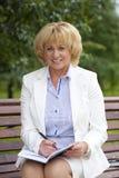 Portret van rustige rijpe vrouw in het de zomerpark Royalty-vrije Stock Afbeeldingen
