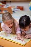 Portret van schoolmeisjes die een sprookje lezen Stock Afbeeldingen