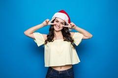 Portret van schoonheids gelukkige vrouw in de hoed van Kerstmissanta over blauwe achtergrond royalty-vrije stock foto