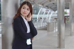 Portret van schoonheids jonge Aziatische onderneemster in kostuum dat en zich ver weg bevindt bekijkt bij Het denken en nadenkend stock foto