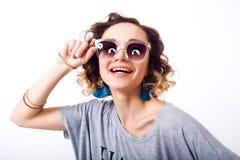 Portret van schoonheidsvrouw in zonnebril luchtkus, krullend haar, manieruitrusting, jonge hipster Stock Fotografie