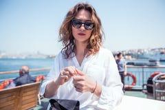 Portret van schoonheidsvrouw in zonnebril luchtkus, krullend haar, manieruitrusting, jonge hipster Royalty-vrije Stock Fotografie