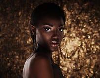 Portret van sensuele jonge Afrikaanse vrouw tegen gouden achtergrond royalty-vrije stock fotografie