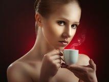 Sexy vrouw die van een hete kop van koffie op een donkere achtergrond geniet Royalty-vrije Stock Foto
