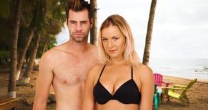 Portret van sexy wit millennial paar die zich onder palmen bij het strand bevinden Royalty-vrije Stock Foto's