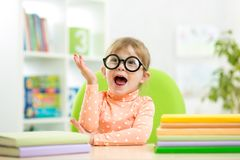 Portret van slim jong geitjemeisje met boeken binnen stock foto
