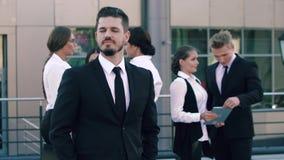 Portret van slim-kijkt bedrijfsmens die de camera en de groep bedrijfsmensen bekijken die hun zaken in doen stock footage