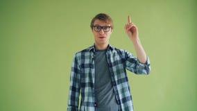 Portret van slimme kerel die idee hebben die vinger opheffen en het bekijken camera glimlachen stock videobeelden