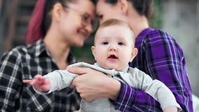 Portret van snoepje weinig baby stellen die camera vrouwelijk paar bekijken op achtergrond stock videobeelden