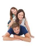 Portret van speelse familie die elkaar opstapelen Stock Afbeeldingen