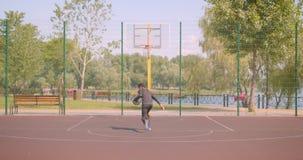 Portret van sportieve Afrikaanse Amerikaanse mannelijke basketbalspeler die een bal werpen in een hoepel in openlucht op het hof stock video