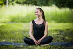Portret van sportieve vrouw die uitrekkende oefeningen in park doen alvorens op te leiden Vrouwelijke atleet die voor jogging voo stock foto