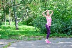 Portret van sportieve vrouw die uitrekkende oefeningen in park doen alvorens op te leiden Vrouwelijke atleet die voor jogging voo royalty-vrije stock afbeelding