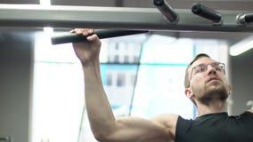 Portret van sportman, die een inspanning in breed-greep lat pulldown in moderne gymnastiek heeft stock video