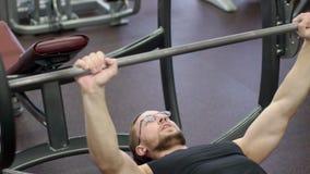 Portret van sportmannen, dat een inspanning in barbell ench persen in moderne gymnastiek heeft stock footage