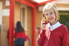 Portret van Student Wearing Uniform Eating Apple royalty-vrije stock fotografie
