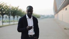 Portret van succesvolle Afrikaanse Amerikaanse zakenman die met smartphone zich dichtbij de bureaubouw en onderzoeken bevinden stock video