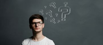 Portret van thinkng jonge kerel met vraagteken boven zijn hoofd royalty-vrije stock foto