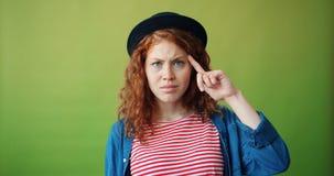 Portret van tiener die vinger verdraaien bij hoofd die dwaasteken het uitspreiden handen maken stock footage