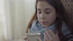 Portret van tiener die in warme sjaal wordt verpakt die een kop van hete thee in handen houden Het meisje voelt slecht, is zij zi stock videobeelden