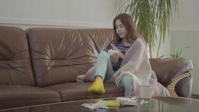 Portret van tiener in een deken wordt verpakt die haar neus in een servetzitting thuis blazen op de leerbank die Het meisje stock video