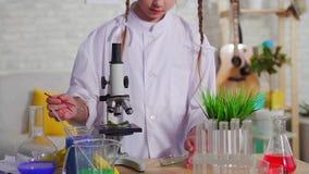 Portret van tiener het kijken door een microscoop, een schoolproject dicht omhoog stock videobeelden