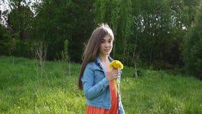 Portret van tienermeisje met gele paardebloemenbloemen in het park stock videobeelden