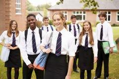 Portret van Tienerstudenten in Eenvormige Buitenschoolgebouwen stock foto's