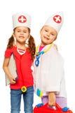 Portret van twee artsen die met medische hulpmiddelen spelen Stock Foto
