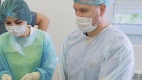 Portret van twee artsen en verpleegster in steriele maskers en kleren tijdens chirurgie in werkende ruimte stock video