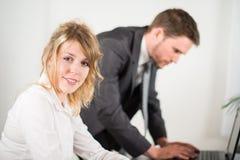 Portret van twee bedrijfsmensen die in bureau met computer samenwerken Stock Foto's