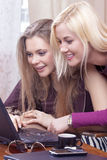 Portret van Twee Emotionele Kaukasische Meisjes met Laptop Computer die Pret hebben binnen stock foto's