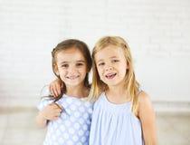 Portret van twee gelukkige glimlachende jonge meisjes royalty-vrije stock afbeeldingen