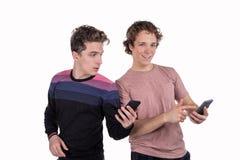 Portret van twee gelukkige jonge mensen die mobiele die telefoons met behulp van over witte achtergrond worden geïsoleerd royalty-vrije stock foto's