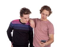 Portret van twee gelukkige jonge mensen die mobiele die telefoons met behulp van over witte achtergrond worden geïsoleerd stock foto