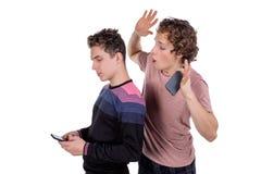 Portret van twee gelukkige jonge mensen die mobiele die telefoons met behulp van over witte achtergrond worden geïsoleerd royalty-vrije stock afbeelding