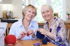 Portret van Twee Hogere Vrouwelijke Vrienden die thuis samen breien stock afbeeldingen