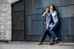 Portret van twee jonge en aantrekkelijke vrouwen die zich naast de muur bevinden stock foto