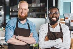 portret van twee jonge multi-etnische eigenaars van koffiewinkel in schorten die zich met gekruiste wapens bevinden royalty-vrije stock foto's