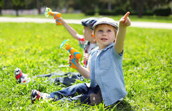 Portret van twee jongenskinderen die op gras het spelen zitten Stock Fotografie