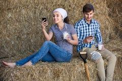 Portret van twee landbouwers die een pauze in het hooi nemen en Th hebben stock fotografie