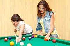 Portret van twee meisjes die binnenbiljart spelen royalty-vrije stock afbeeldingen
