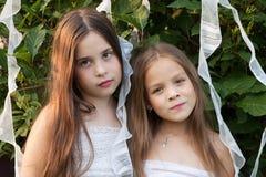 Portret van twee meisjes in witte kleding in de tuin Royalty-vrije Stock Afbeeldingen