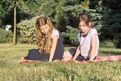 Portret van twee meisjesvrienden 7, 8 jaar oude zittings op het gras in het park royalty-vrije stock afbeelding