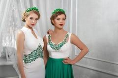 Portret van twee modellen, donkerbruin, glimlachend blonde in witte kleding stock foto