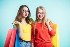 Portret van twee mooie jonge glimlachende vrouwen op blauwe achtergrond De jeugd, vriendschap, het winkelen, levensstijl royalty-vrije stock afbeelding