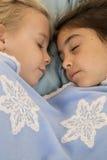 Portret van twee mooie jonge meisjes in slaap in bed Stock Afbeeldingen