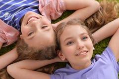 Portret van twee mooie meisjes die op groen tapijt liggen en camera bekijken stock afbeelding